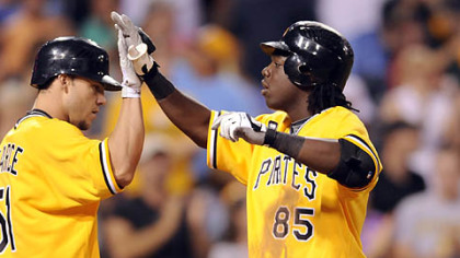Pirates' Lastings Milledge is congratulated by teammate Steve Pearce after hitting a home run against the Reds in the fourth inning.