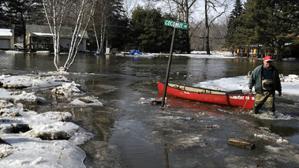 "Dave Porada pulls his canoe across Neshannock Creek near a flooded Coconut Drive. His house is to the left, where he has lived since the mid-1970s. He said, ""You lie in a river valley -- you live with it or you leave."" Mr. Porada said about 12 or 13 houses were affected by the dam of ice, but only six houses have year-round residents. He said his basement is completely flooded."