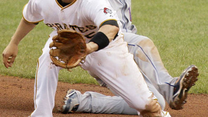 Pirates second baseman Ramon Vazquez, front, takes the late relay throw as Mets first baseman Fernando Tatis slides into second with an eighth-inning-double yesterday.