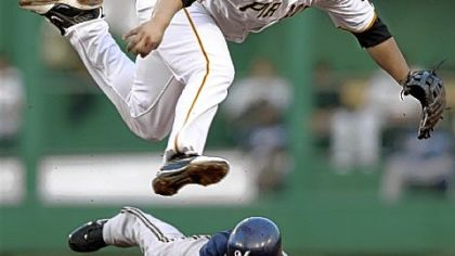 Second baseman Delwyn Young avoids Milwaukee's McGehee to turn a double play in the second inning last night at PNC Park.
