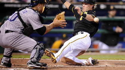 The Pirates&#039; Nate McLouth slides safely into home plate against Rockies catcher Chris Iannetta in the sixth inning last night.