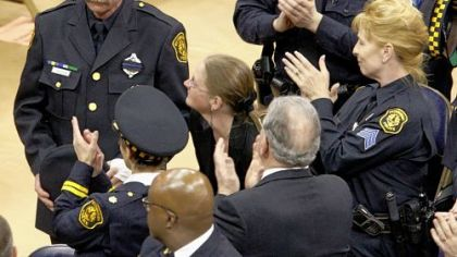 Officer Timothy McManaway, left, is honored during yesterday&#039;s memorial service. He was wounded in the hand while helping downed Officer Eric G. Kelly.