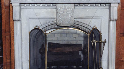 The coat of arms in the center of this carved stone fireplace depicts a knight with a branch hovering above him.