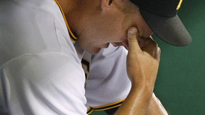 Pirates pitcher Steven Jackson sits in the corner of the dugout after giving up five runs, four of them earned, to the Diamondbacks in the 12th inning of last night's 11-6 loss at PNC Park.