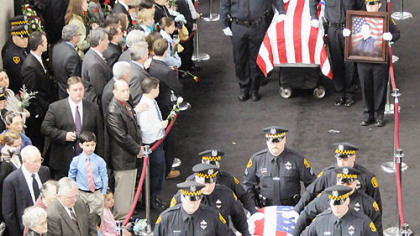 Pittsburgh Police pallbearers carry the caskets of slain officers, from front, Stephen J. Mayhle, Paul J. Sciullo II and