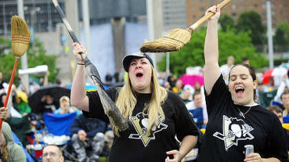 The sweep is on ... Geralyn Holby of Irwin, left, and Nicole Agulia, right, hold their brooms and cheer the Penguins in game 4 against Carolina at the Jumbotron at the Mellon Arena Tuesday night.