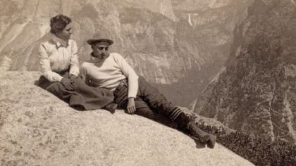 Lounging on Eagle Rock in Yosemite National Park, circa 1902, with Half Dome and Nevada Falls in the background.