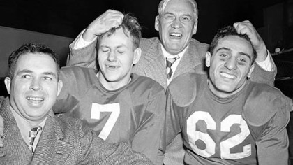 Coach Jimmy Conzelman musses the hair of Charley Trippi, right, and Elmer Angsman after the 1947 title game.