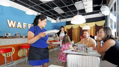 Waitress Zena Ruiz serves up waffles to the Peterson family of West Mifflin, who stopped for breakfast on their way to the zoo.