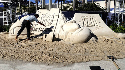 Mark Mason of Team Sandtastic puts the finishing touches on a sand sculpture at the NFL On Location Beach House outside the entrance to Raymond James Stadium yesterday in Tampa, Fla.