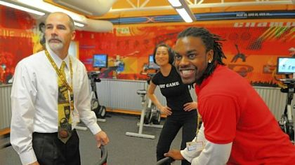 Jay Hope, left, associate executive director of the Penn Hills YMCA, and fitness coach Lomel Patterson, right, demonstrate an interactive snowboarding video game in the new XRKade at the Penn Hills YMCA on Friday. In the background is  XRKade director Andrea Oh. The XRKade, a new facility at the Penn Hills YMCA, uses video games to attract  children 9-12 to physical activity.