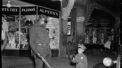 "Small boy in police officer's uniform with Prince ""Big Blue"" Bruce on beat outside Alpern's clothing store with beauty parlor next door, c. 1952."
