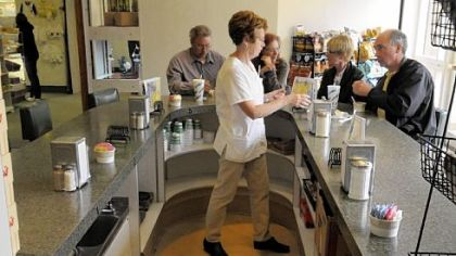 Anita Schock, of Finleyville, waits on her customers in one of three U-shaped counters at the snack shop in St. Clair Hospital. She has worked there for more than 17 years.