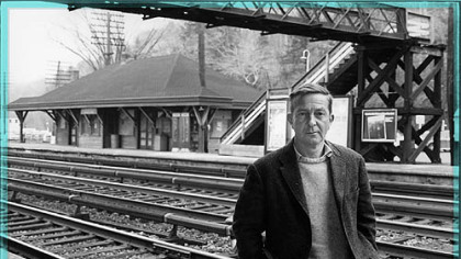 John Cheever stands at the kind of commuter station often found in his fiction.
