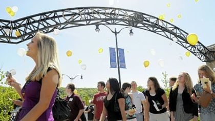 Graduating seniors at Geneva College release balloons while walking through the brand-new arch at the campus entrance.