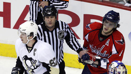 An official separates Sidney Crosby and Alex Ovechkin yesterday.