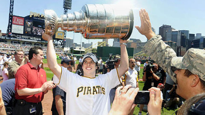 Sidney Crosby hoists the Stanley Cup while wearing a Pirates jersey as members of the Stanley Cup champion Pittsburgh Penguins attend a baseball game between the Pittsburgh Pirates and the Detroit Tigers.