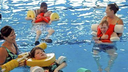 Children at Allegheny Valley School in Robinson take part in Aquatic Therapy class. From left are Elizabeth Mink with client Carol Valecko; Tenieda Greene with client Danny Barcelona; and Chris Hurt with client Sean Malley. The late Myron Cope gave trademark rights for his Terrible Towel to the school. Royalties from sales are used to benefit the school.