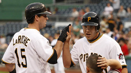 Pirates third baseman Andy LaRoche is greeted at home by teammate Steve Pearce after hitting a two-run homer in the second inning as Diamondbacks catcher Miguel Montero rubs his head.