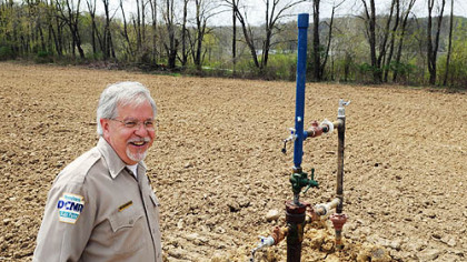 William Wasser, Maurice K. Goddard State Park manager, at the Hill No. 1 well head, which is just off the bike trail along the shores of Lake Wilhelm. By summer, the well will be nearly invisible in the middle of a cornfield.