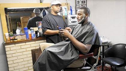 DeJuan Blair keeps up with his text messages as he gets a haircut by his friend Greg Mitchell in Monroeville yesterday. Blair slipped to the second round of the NBA draft and was chosen by the San Antonio Spurs.