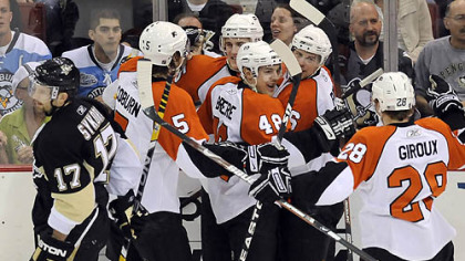 Flyers teammates congratulate Darroll Powe on his third-period goal.