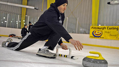 "Jerrett Covington, 30, of Moon, delivers the stone during a ""learn to curl"" class at the Robert Morris University Island Sports Center on Neville Island."