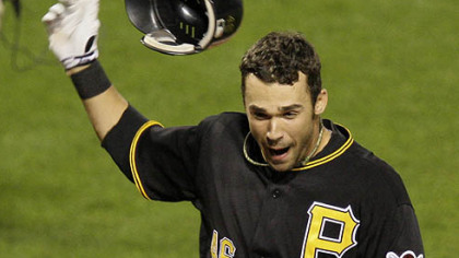 Pirates outfielder Garrett Jones throws off his batting helmet as he touches home plate after hitting a walk-off 14th-inning solo home run off Giants pitcher Bob Howry.