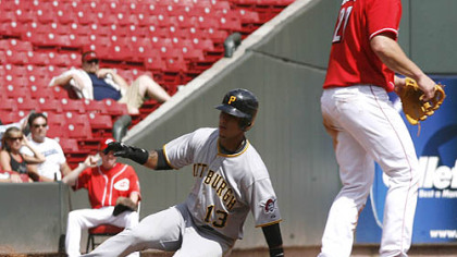 Pirates shortstop Ronny Cedeno slides into third base for a triple past Reds third baseman Scott Rolen in the seventh inning of the first game.