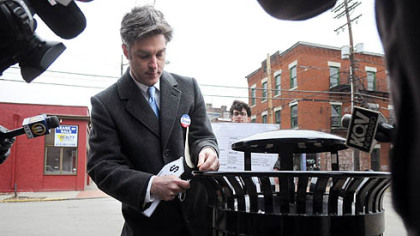 City Councilman Patrick Dowd ties a $1,010 price tag onto a city garbage can along Carson Street on the South Side yesterday.