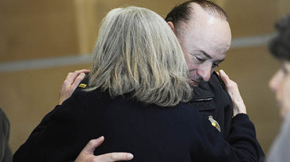 Lt. Michael Scott receives a hug from Beth Pittinger, director of the Citizen Police Review Board, after a news conference yesterday afternoon about the officers' shooting.