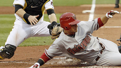 Diamondbacks outfielder Garardo Parra slides past Pirates catcher Ryan Doumit trying to score from first base on a double by third baseman Mark Reynolds in the third inning. No call was made on the play, but Parra was called out after Doumit later tagged him.