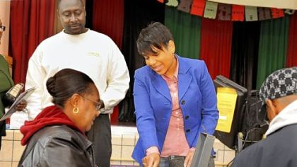 Democrat  Carmen Robinson shows her voter registration card while casting her ballot yesterday.