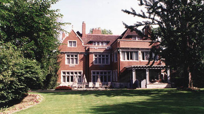 The large lawn behind the mansion includes a flagstone patio, a red brick path and lots of mature trees.