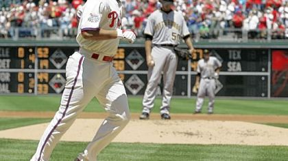 The Philadelphia Phillies' Pedro Feliz heads to home after hitting a grand slam off Pirates starter Virgil Vasquez, rear, in the first inning yesterday in Philadelphia.