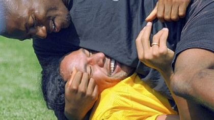 Troy Polamalu gets &quot;help&quot; with stretching from teammate Ryan Clark yesterday at training camp.