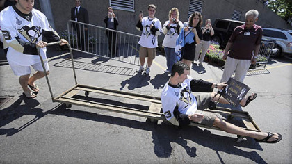 Bill Guerin, the oldest Penguin, is carted out of Mellon Arena yesterday by Kris Letang before the parade.