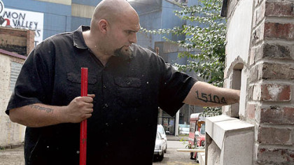Braddock Mayor John Fetterman pokes around a community bread oven as it was being readied for a trial run in September.