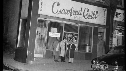 Three men standing outside of the Crawford Grill No. 1.