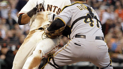 Giants first baseman Jesus Guzman is forced out at home plate by Pirates catcher Ryan Doumit during the second inning.