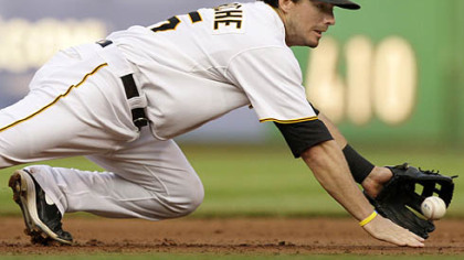 Pirates third baseman Andy LaRoche makes a diving stop on a ground ball by Diamondbacks infielder Ryan Roberts during the second inning. LaRoche recovered to make the putout on Roberts at first.