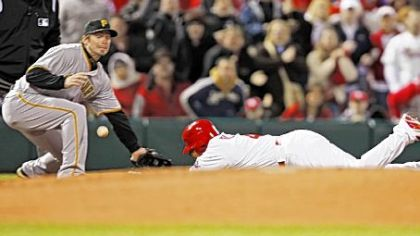 St. Louis' Yadier Molina dives into third base with a triple in the second inning as the ball caroms away from Pirates third baseman Andy LaRoche.