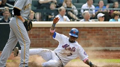 Pirates reliever John Garbow, left, returns to the mound as Mets' Jose Reyes, right, scores on teammate Carlos Beltran's eighth-inning, two-run double to deep left field.