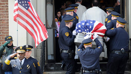 Pittsburgh Police Chief Nate Harper, front left, salutes as the flag-draped casket of Officer Paul J. Sciullo II is carried into St. Joseph Church in Bloomfield for his funeral yesterday.