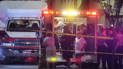 Emergency workers tend to victims of last night's shooting.