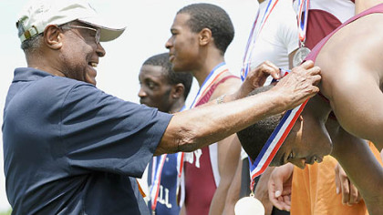 After winning the Class AAA 100-meter dash yesterday in Shippensburg, Pa., Peabody's Pierre Carr, right, receives his gold medal from Allderdice alum Herb Douglas. Douglas, 87, was the first athlete from the City League to win both the 100 and 200 in 1940. Carr repeated his feat yesterday.