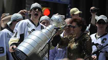 Evgeni Malkin cheers after his parents, Vladimir and Natalia, drank champagne from the Stanley Cup.