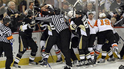 Referees separate Penguins and Flyers payers at the end of the first period.