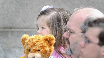 Her police teddy bear in hand, a girl waits to see the caskets of the slain police officers.