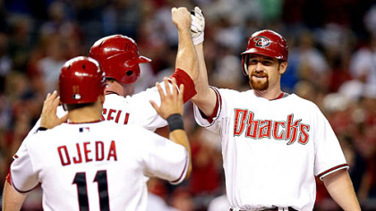 Diamondbacks first baseman Chad Tracy, right, gets high fives from first baseman Josh Whitesell, middle, and infielder Augie Ojeda after hitting a three-run home run in the seventh inning.
